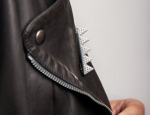 Close up of side of leather jacket with brooch named 126 53