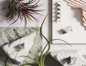 Still life picture of Veritume jewellery together with stones, green flowers and marble, white and grey background