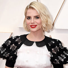 "Blink and you'll miss the statement accessory Lucy Boynton's hairstylist Jenny Cho glued to the actor's hairline: pearls. ""[The] inspiration was Coco Chanel herself — French-chic-meets young Hollywood,"" Jenny Cho tells Allure. This makes sense considering makeup artist Jo Baker is responsible for the bold red lip and spider-like lashes (both by Chanel) that complete the look."