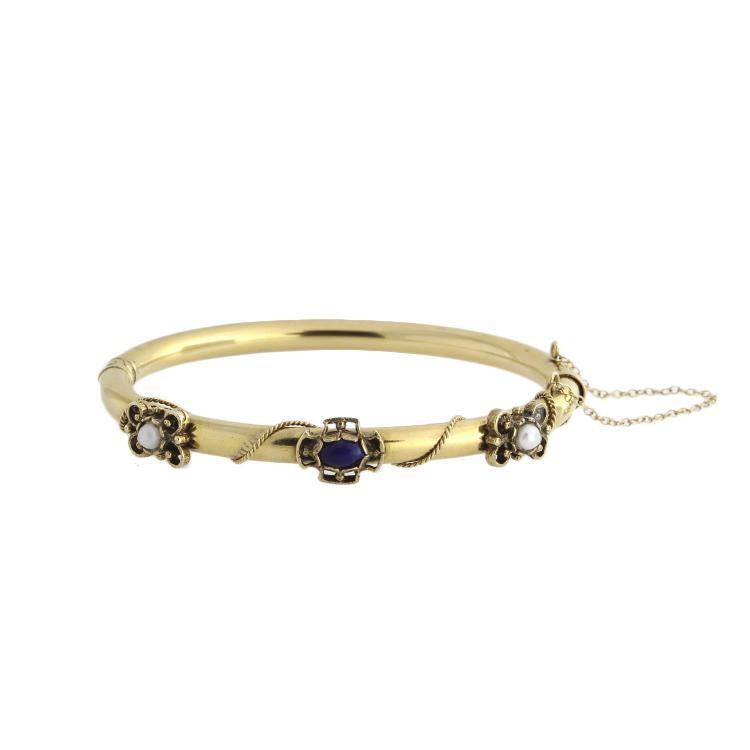 This bracelet features small pearls and a lapis stone in the center.