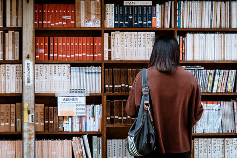 Japanese student from a high school looking for a book in a library.