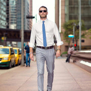 man wearing cache belt with suit pants and white button down shirt in a city
