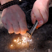 using the folding ceramic knife and a ferro rod to create large sparks to start a fire