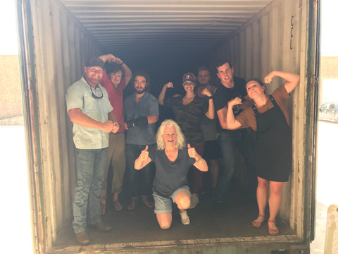 BJ with family members in an empty shipping container after unloading a shipment of SnapIt Boards