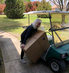 BJ Strahan loads a box of SnapIt Boards onto a golf cart