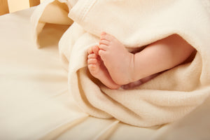 Cherub's Blanket Organic Cherub's Blanket wrapped around a newborn with baby feet showing. Visit us at www.cherubsblanket.com