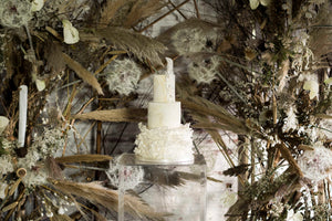 Voluminous three tier wedding cake pictured at Cheshire's Dorfold Hall against a contemporary dried flower installation