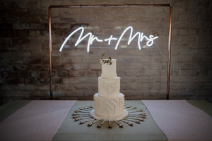 "Macrame detail wedding cake in contemporary setting framed by ""Mr and Mrs"" neon lights"