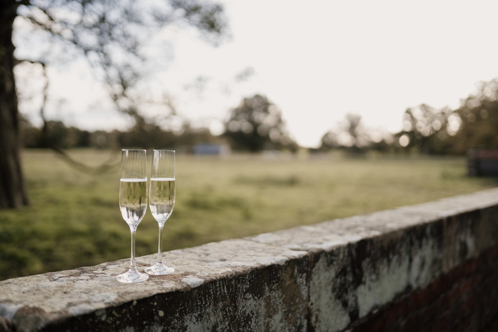 Pair of filled champagne glasses on a wall.  Lancashire and Cheshire weddings