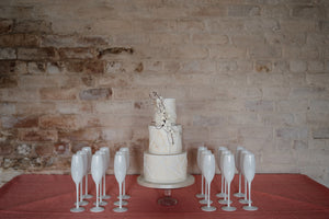 Modern wedding cake against whitewashed wall with white champagne glasses. Wedding cakes for Cheshire, Lancashire, Merseyside and Yorkshire