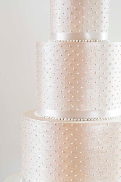 Champagne coloured, budget friendly deep tiered modern wedding cake in a simple classic design with sharp edges and piped pearls