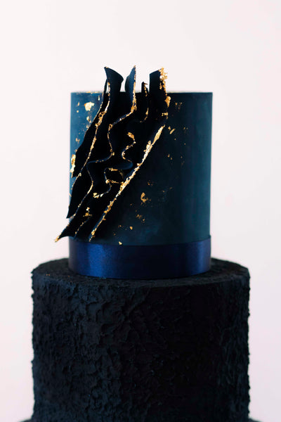 Deep tiered navy blue wedding cake.  Middle tier has rough textured icing, top tier is smooth with edible voile