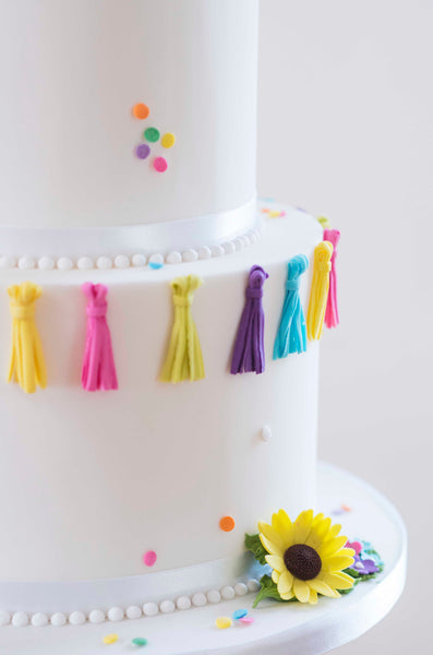 Brightly coloured sugar tassles contrast with pristine white icing on a great value wedding cake.