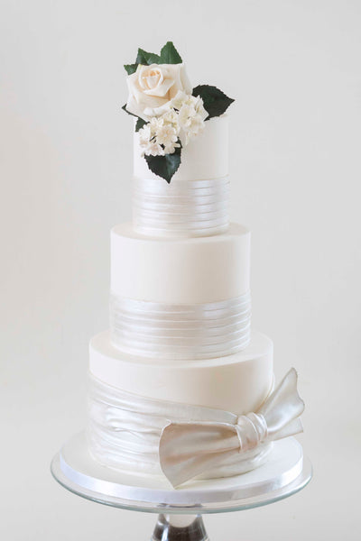 Three tier ivory wedding cake partially wrapped with pearlescent satin effect sugarpaste, topped with a white sugar rose