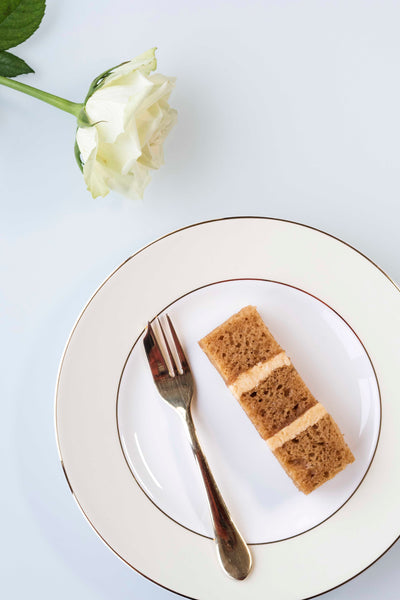 Single slice of toffee wedding cake with salted caramel buttercream on plate with gold fork and white rose