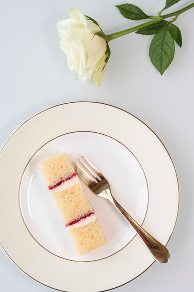 Single slice of vanilla sponge wedding cake with raspberry conserve on plate with gold fork and white rose