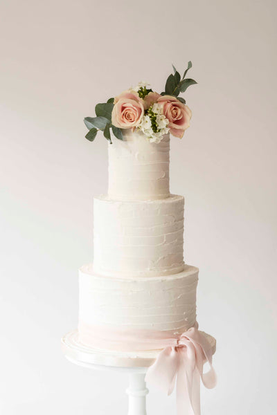 Buttercream effect textured wedding cake styled with fresh flowers and foliage and silk ribbon