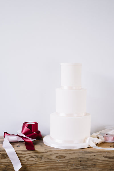 Our version of a naked wedding cake. Finished in smooth sugarpaste and neutral ribbon.