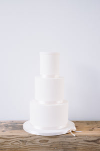 Our version of a naked wedding cake. Finished in smooth sugarpaste and neutral ribbon