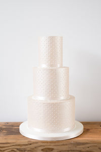Simple and understated deep tiered modern wedding cake with sharp edges in a luxurious champagne colour with piped pearls