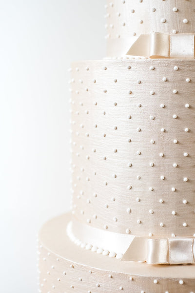 Simple deep tiered modern wedding cake in a luxurious champagne colour with piped pearls and satin ribbon.