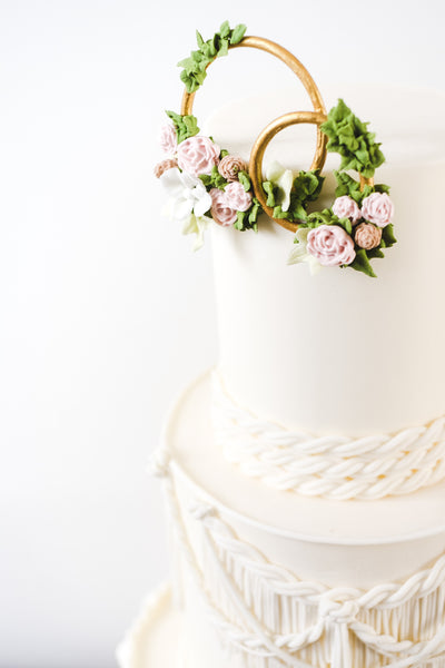 Gold rings decorated with sugar flowers on top of boho style wedding cake with sugar macrame lace