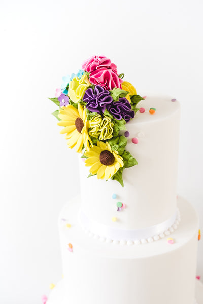 3 tier white wedding cake with contrasting colourful tassles on the base tier and matching ruffled top with sugar rudbekia.