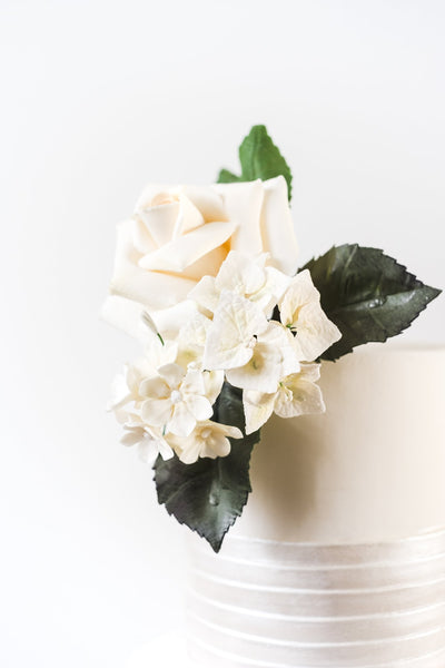 Top of contemporary ivory wedding cake with realistic white sugar rose, vivid green foliage and blossom flowers