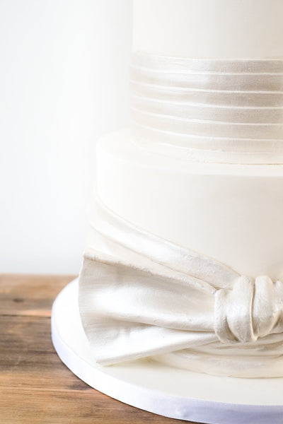 Oversized edible satin effect knot on a modern deep tiered ivory wedding cake with sharp edges