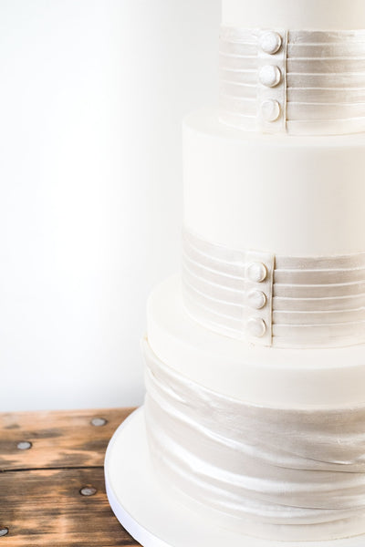 Deep tiered wedding cake decorated with bands of satin look sugarpaste with button detail like the back of a wedding dress.