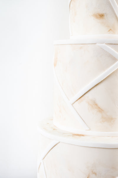 Coastal style modern, affordable wedding cake with a delicate spray of sugar flowers