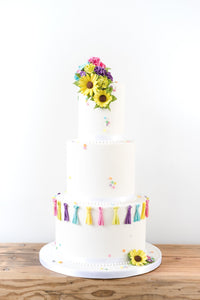 Contemporary white deep tiered wedding cake with pops of bright colour from sugar tassles and yellow sugar sunflowers