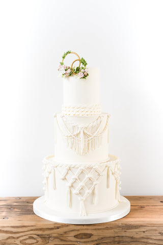 Three tier ivory boho wedding cake dressed with sugar macrame lace, topped with decorated gold rings