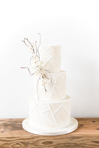 Modern wedding cake with a coastal, sun-bleached design and delicate sugar flowers