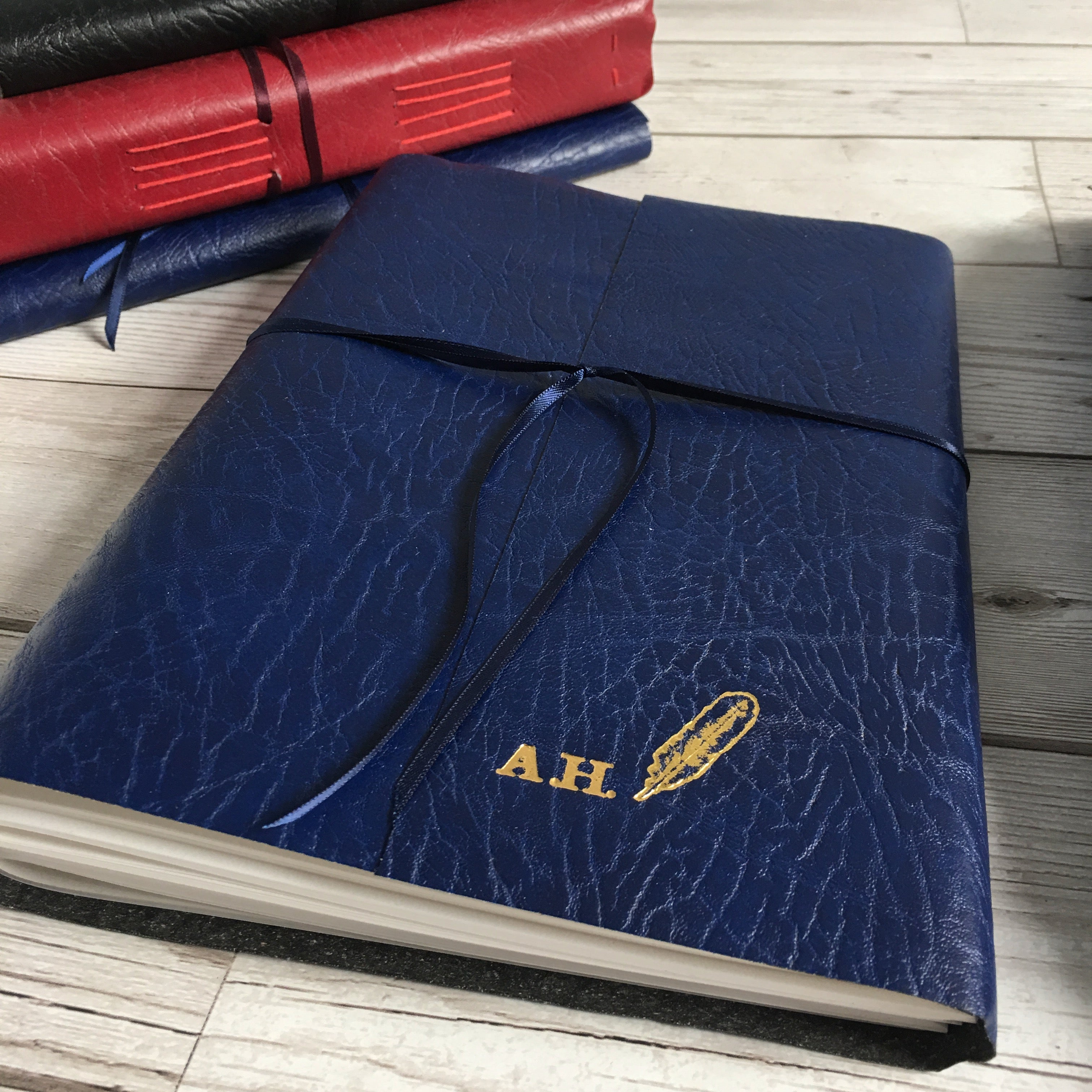 A4 blue leather wraparound journal with two initials and quill embossed in gold