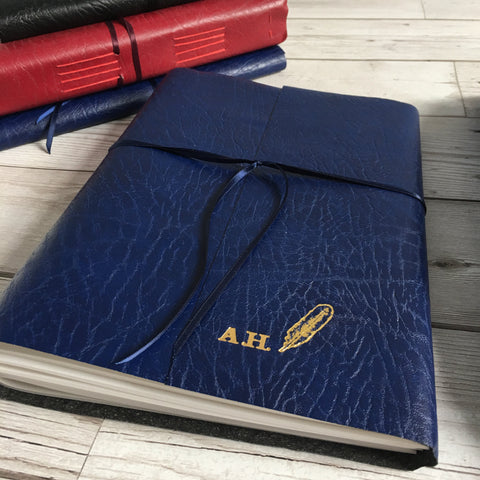 A5 blue leather wraparound journal tied with blue ribbon, with quill and personalised initials embossed in gold on cover