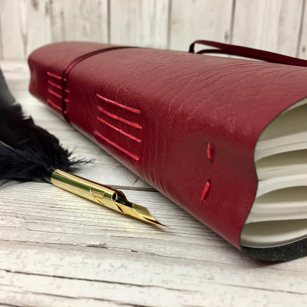 Red leather wraparound notebook with pages sewn in four sections using long stitch in red thread