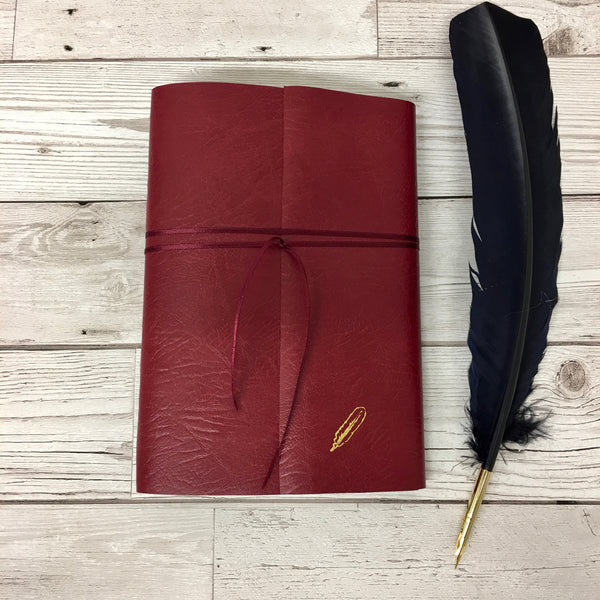 Red leather wraparound notebook embossed with gold quill on bottom right of cover