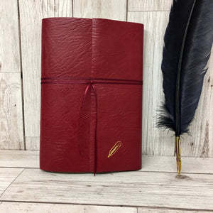 A4 Red leather wraparound journal with matching ribbon and gold quill on bottom right of cover