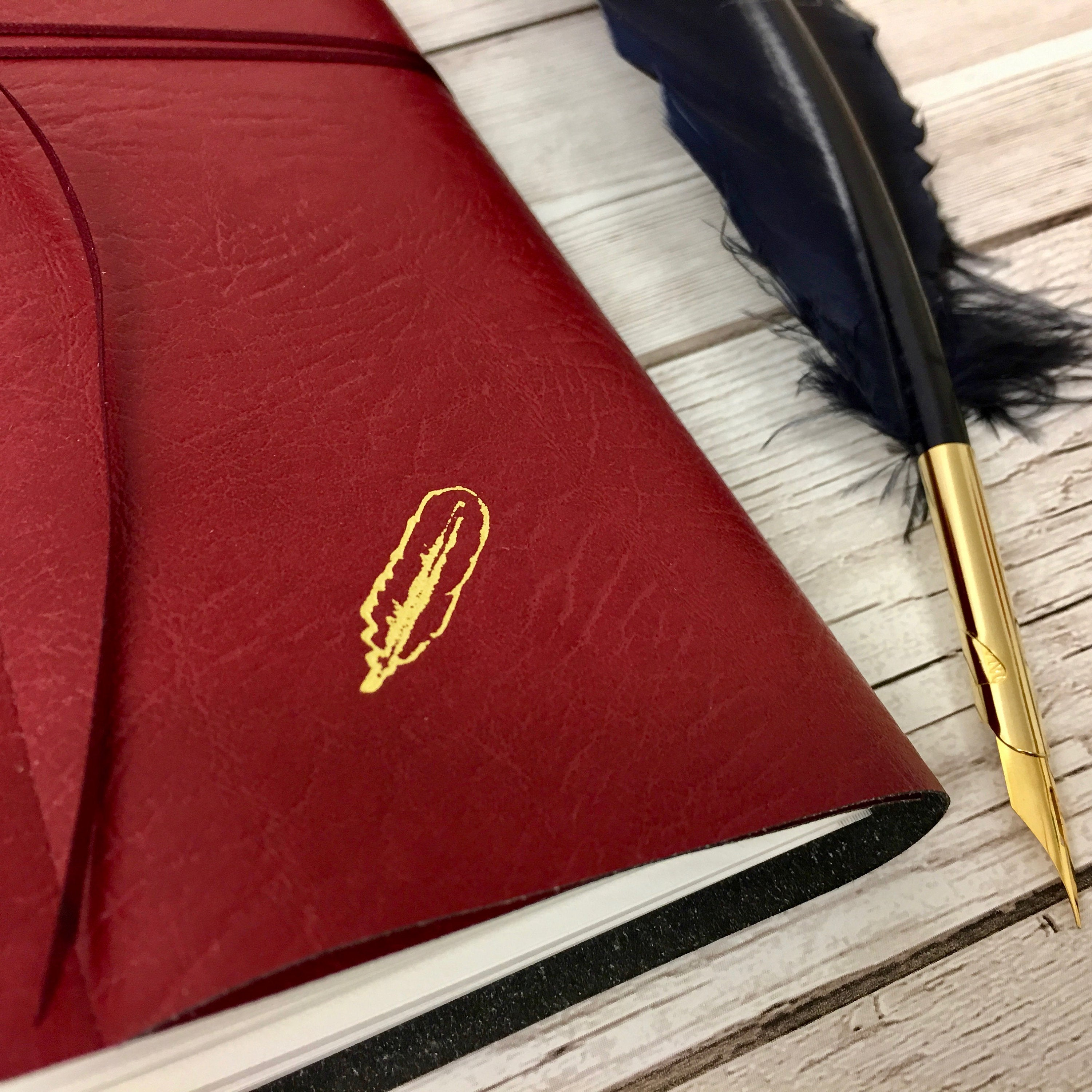 Close up of gold embossed quill on red leather cover