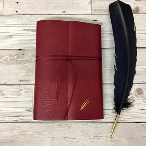 Red leather wraparound notebook with gold quill lying on bleached floorboards