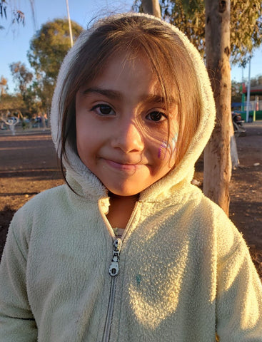 Indigenous little girl smiling at the camera and the sunshine covering her smile