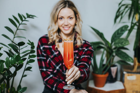 Cami holding low alcohol, low calorie, mindful cocktail. Wild Life Botanicals low alcohol sparkling wine.