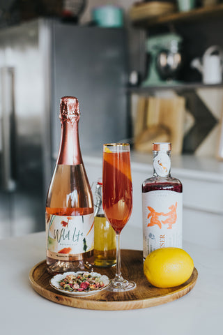 Amour cocktail ingredients, rose and honey water, Wild Life Botanicals Blush sparkling wine, and Sensor Love