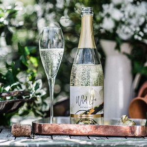 Wild Life Botanicals Nude open bottle on table with full glass of fizz. Ultra-low alcohol, low calorie and low carb sparkling wine. Healthy wine alternative.
