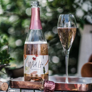 Wild Life Botanicals Blush 75 open bottle on table with full glass of fizz. Ultra-low alcohol, low calorie and low carb sparkling wine. Healthy wine alternative.