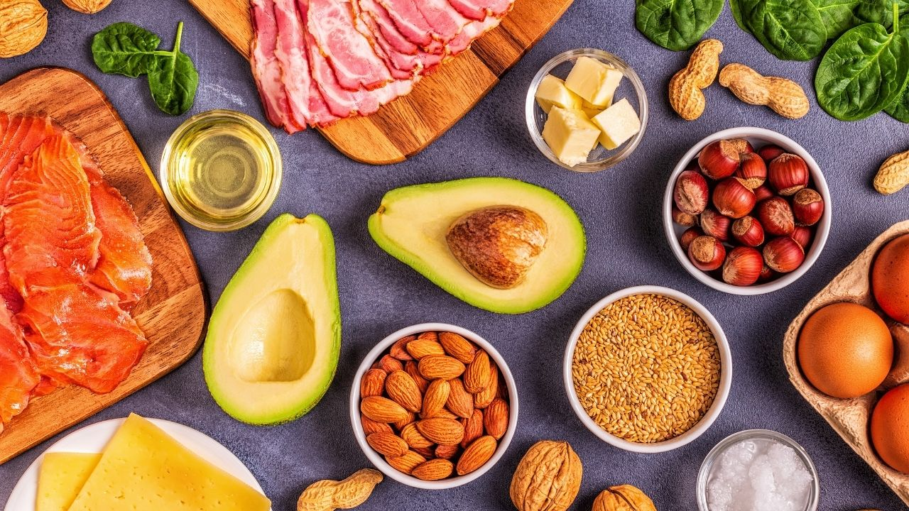 Low carb foods spread on a table including avocado, meat, fish, eggs, nuts, seeds, dairy, and spinach