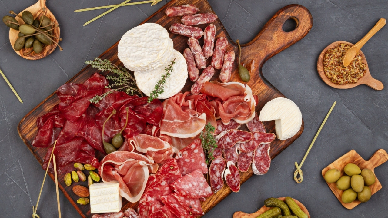 Keto charcuterie board with salami, cheese, olives, and pickles