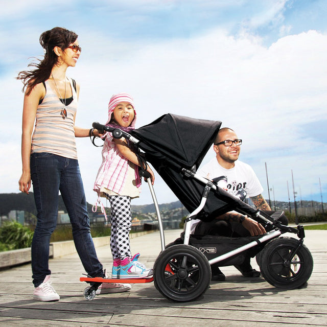 Family walking along the boardwalk with theMountain buggy freerider attached to an urban jungle in black_black
