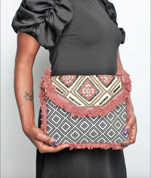 Woman carrying the 'Gasira' Large Fold-over Clutch, a bold pattern accessory